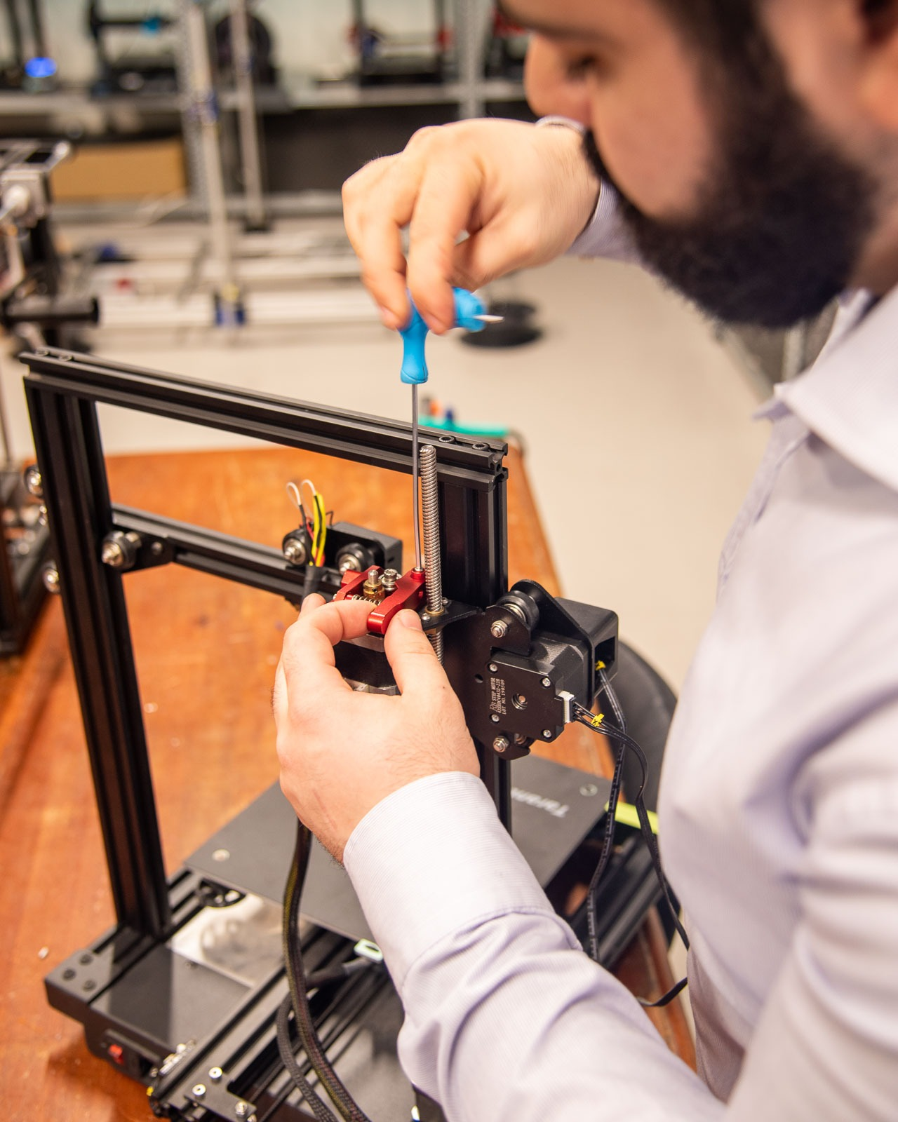 Invent 3D employee fixing 3D printer